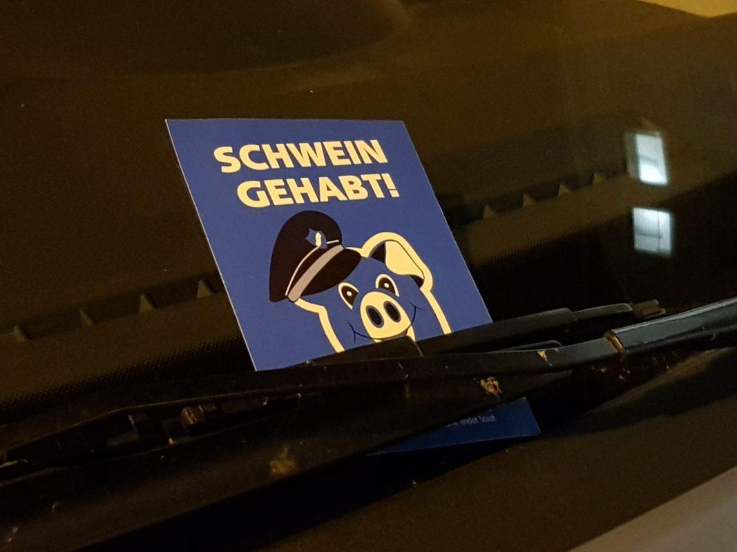 """Die blaue """"Schwein gehabt"""" - Karte am Auto eines Parksünders. Foto: Dirk Flieger"""