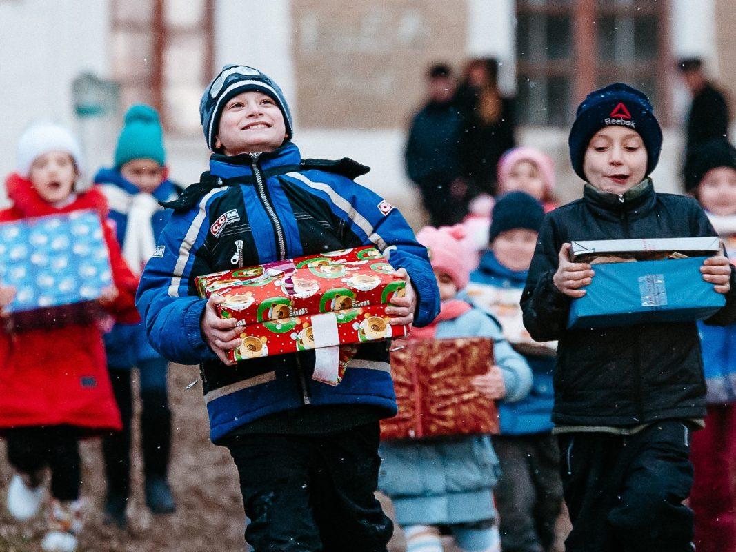 Kinder rennen nach einer Schuhkartonverteilung in der Ukraine freudig nach Hause. Foto: David Vogt
