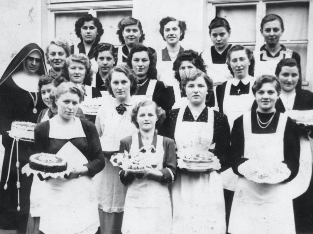 Junge Frauen nehmen in Waldsachsen nach ihrer Schulzeit an einem Hauswirtschaftskurs / Kochkurs / Backkurs teil, der von einer der Oberzeller Schwestern aus Schweinfurt (Theresienheim) geleitet und im Alten Kindergarten durchgeführt wurde. Dez. 1952. Foto: Familie Mai, Bayerhöfer + Sammlung Oberlehrer Göbel.