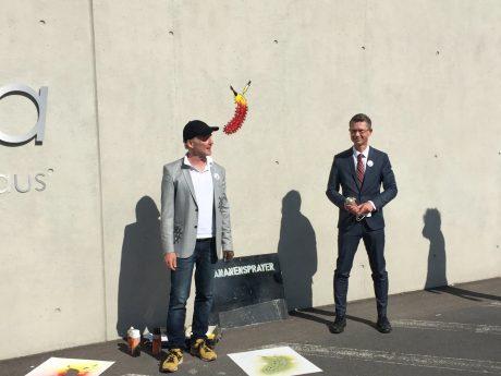 """Bananensprayer"" Thomas Baumgärtel und Schirmherr der Street-Art-Aktion OB Sebastian Remelé vor der Impfbanane am Leopoldina-Krankenhaus Foto: Iris Muffert-König / Kunstverein Schweinfurt e.V."