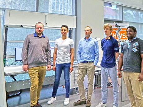 """Das Team """"RoboPig"""" um Prof. Dr. Tobias Kaupp (Mitte) verfolgt gespannt den Livestream der Award Show. Im Hintergrund ist der Roboterarm zu sehen, mit dem das Team die Aufgabenstellung löste. Foto: Fabian Dax"""