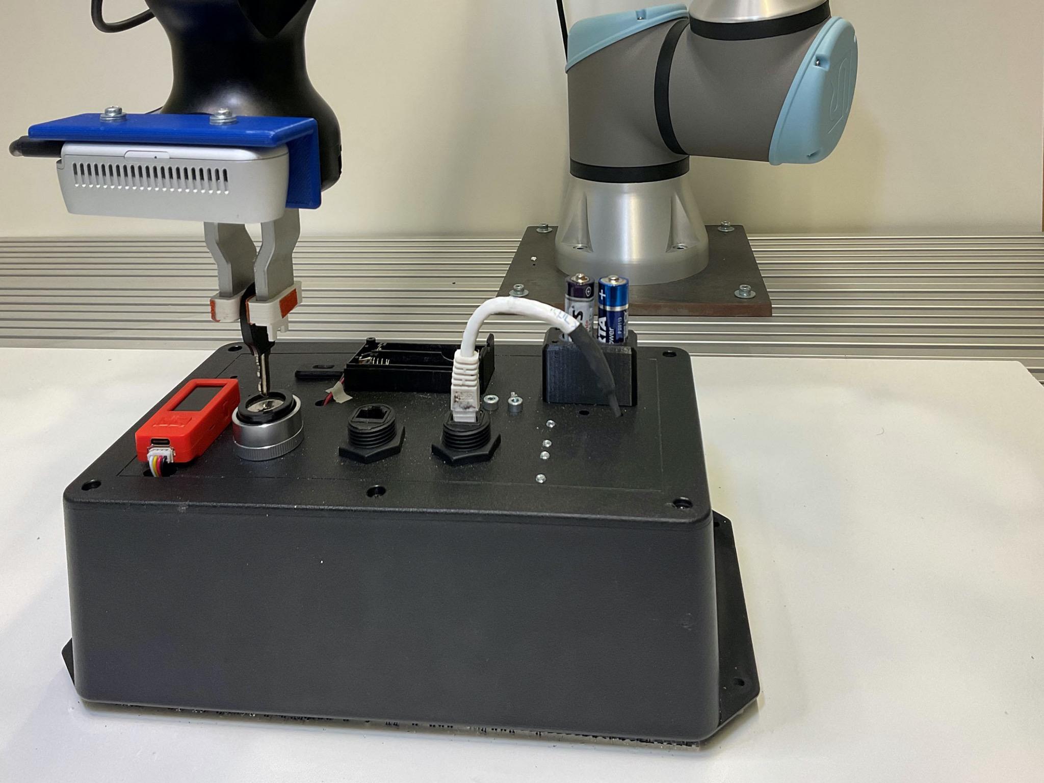 """Der Roboter ist dabei, einen Schlüssel in ein Schloss einzuführen und nutzt dabei seine Feinfühligkeit. Das """"Task Board"""" erkennt die erfolgreiche Durchführung der Aufgaben durch Sensorik und misst gleichzeitig die dafür benötigte Zeit. Foto: Elhasan Mohamed"""